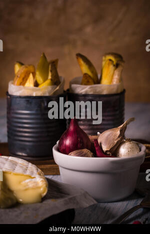 Vertical photo of white bowl full of color onions and garlic cloves. The bowl is placed on blue wooden vintage board - Stock Photo