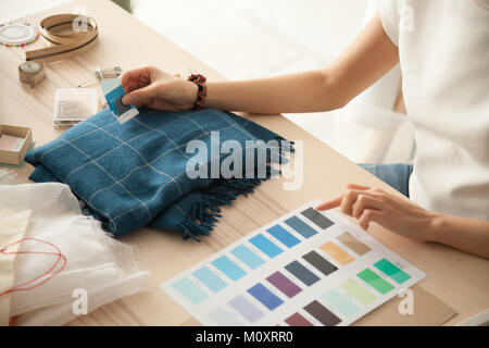 Female fashion designer holding samples choosing color working w - Stock Photo
