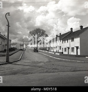 1950s, historical, new social housing....a solitary car parked on an empty road at a modern housing development - Stock Photo