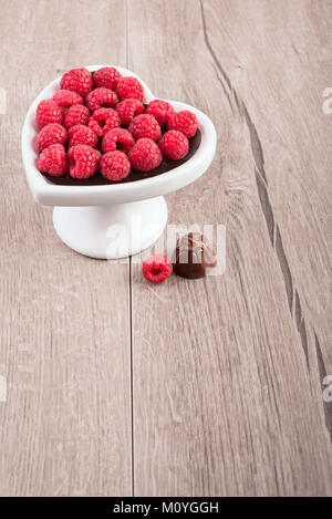 Heart-shaped plate of raspberries in chocolate sauce on a wooden table, text space - Stock Photo