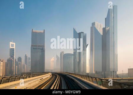 Dubai metro with skyscrapers on either side - Stock Photo