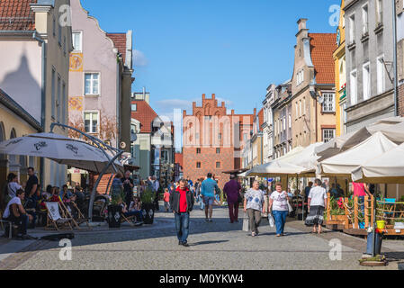 Staromiejska pedestrian street on the Old Town of Olszty city, Poland. View with XIV century city gate called Upper - Stock Photo