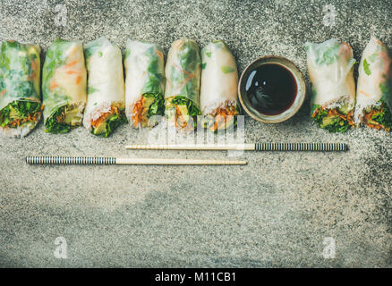 Helathy Asian cuisine. Flat-lay of vegan spring or summer rice paper rolls with vegetables, sauce and chopsticks - Stock Photo