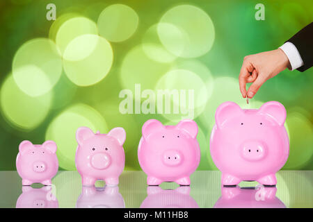 Close-up Of A Businessperson's Hand Inserting Coin In Piggybank - Stock Photo