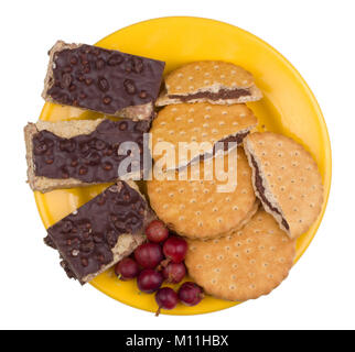 Uneven broken pieces of walnut waffle cake and chocolate chip cookies lie on a yellow plate. Isolated on white top - Stock Photo