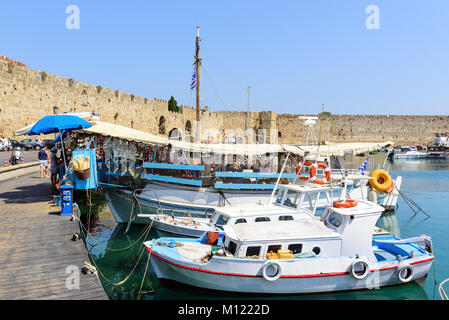 RHODES, GREECE - AUGUST 2017: Traditional Greek fishing boats are staying moored at sea port of Rhodes town on Rhodes - Stock Photo