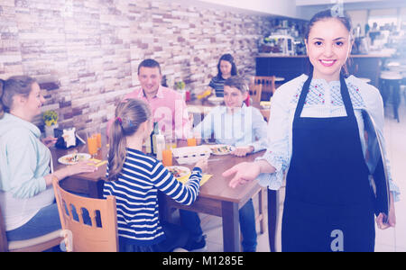 Young hospitable waitress with menu is inviting in cafe. - Stock Photo