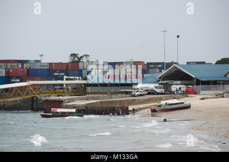 Containers loading onto a container ship in the port of Zanzibar, Tanzania, on a sunny day with dhows in the foreground - Stock Photo