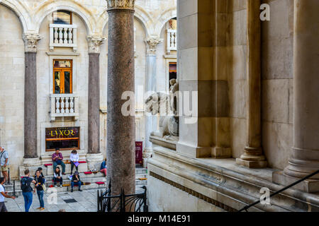 A lion statue outside the Cathedral of Split facing the Peristyle of Diocletian's Palace in Split Croatia as tourists - Stock Photo
