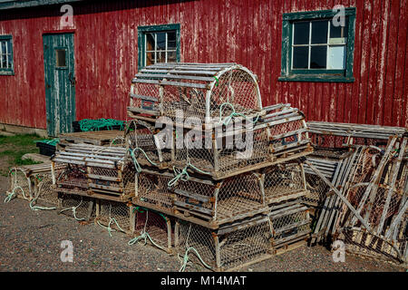 Lobster traps in front of an old red shed. - Stock Photo