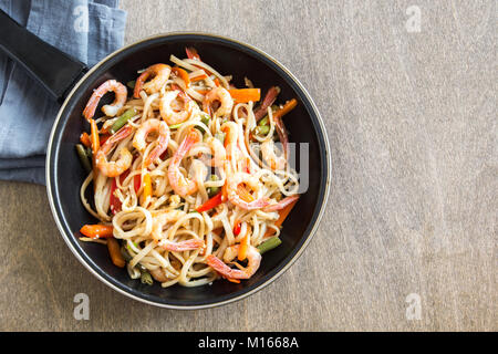 Stir fry with udon noodles, shrimps (prawns) and vegetables. Asian healthy food, meal, stir fry in wok over wooden - Stock Photo