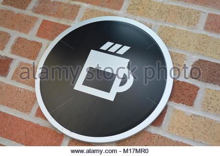Modern circular coffee sign on brick wall - Stock Photo