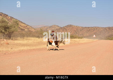 Young,married Himbafrau rides with a small child on a donkey,Kaokoveld,Namibia - Stock Photo