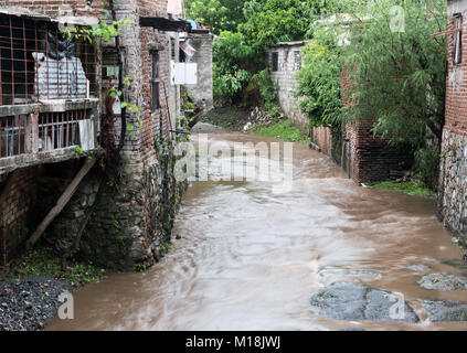 Holguin, Cuba - August 31, 2017: Muddy stream running in between residential areas. - Stock Photo