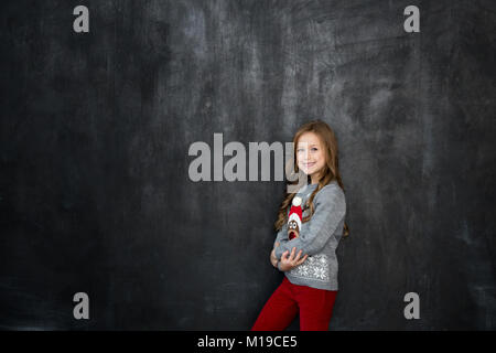 Pretty girl stands on the black background of a chalkboard and smile. background with a free space - Stock Photo