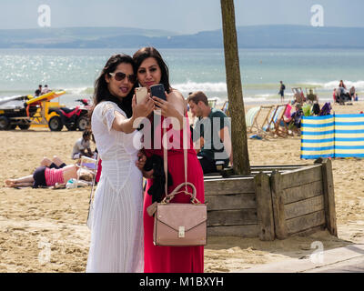 Two smartly dressed young millennial women taking selfies together using smartphones on a beach in late summer. - Stock Photo