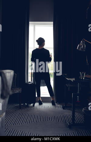 Woman using mobile phone in hotel room - Stock Photo
