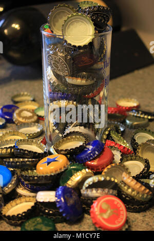 Used beer bottle tops collected after the beer has been drunk and are over flowing from a straight sided half pint - Stock Photo
