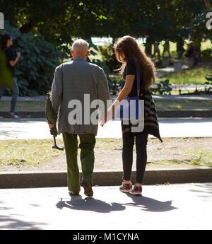 Young girl helping older man to get Fidel Castro memorial ceremony in Havanna Revolationary Park - Stock Photo