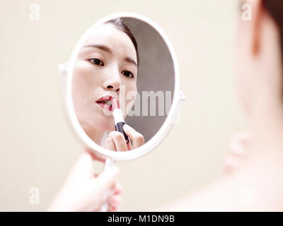 beautiful young asian woman looking at self in mirror while applying lipstick on lip. - Stock Photo