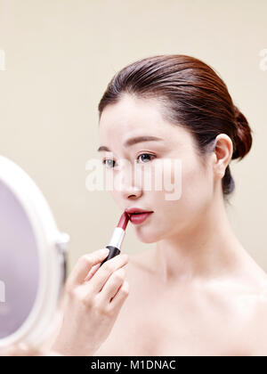 beautiful young asian woman looking in the mirror while applying lipstick on lips. - Stock Photo