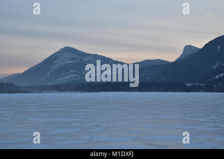 Sunrise over snowy mountains with a frozen lake in the foreground - Stock Photo