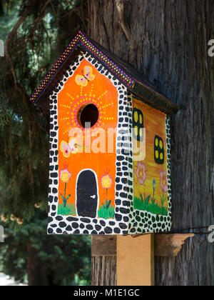 Bright, painted under the multi-storey house, birdhouse on a tree trunk - Stock Photo