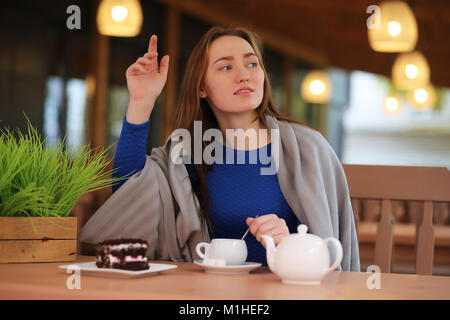 Young girl in cafe sits and drinks tea - Stock Photo