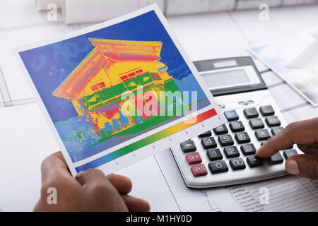 Close-up Of Person Hand Calculating Heat Temperature Using Calculator On Desk - Stock Photo