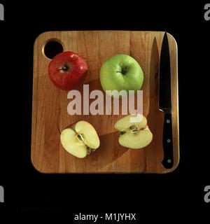 Washington state grown Red Delicious and Granny Smith apples ready to eat on cutting board. - Stock Photo