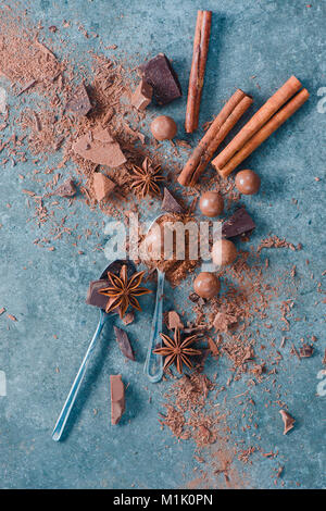 Flat lay with spoons, chocolate pieces, spices, anise stars, cinnamon and cocoa on a stone background. Ingredients - Stock Photo