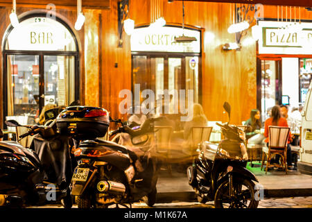 Late night in Paris France at a sidewalk cafe and bar in the Latin Quarter with motorcycles out front and diners - Stock Photo