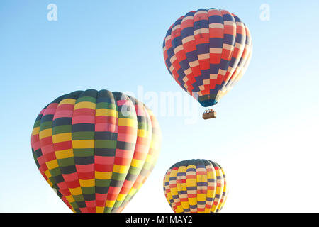 Hot air balloons in flight with vibrant colours against early morning blue sky - Stock Photo