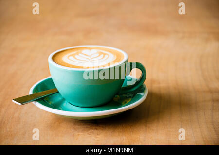 A cup of coffee with latte art of a leaf in the foam with a spoon on a wooden table - Stock Photo