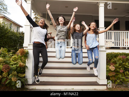 Four young teen girls jumping from front steps of a house - Stock Photo