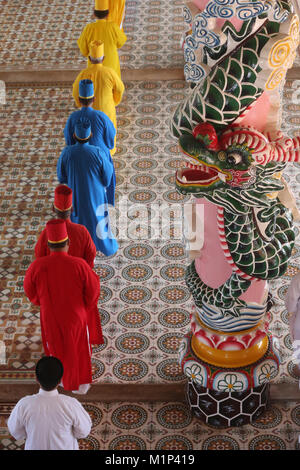 Priests and dragon column, Cao Dai Holy See Temple, Tay Ninh, Vietnam, Indochina, Southeast Asia, Asia - Stock Photo