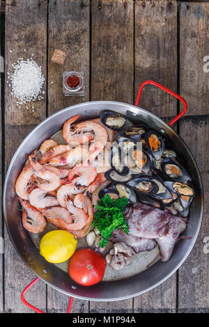 Raw seafood products in paella pan on a wooden table, top view - Stock Photo