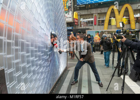 New York, USA. 1st February, 2018. A reporter for NTN24, a Spanish language news channel, interviews tourists posing - Stock Photo