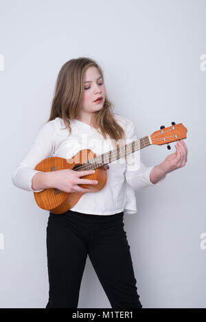 Girl tuning ukulele on white background - Stock Photo