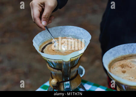 Barista stirs pour over coffee in artisan glass brewer while outdoors - Stock Photo