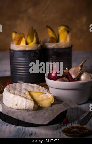 Vertical photo of hot melted camembert cheese on piece of paper and vintage wooden board with bowl full of color - Stock Photo