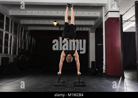 Young Athlete Man Doing Handstand Exercise On Parallel Bar In The Gym - Stock Photo