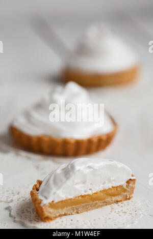 lemon tartlets with white air cream against on wooden table. - Stock Photo