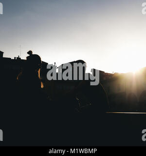 Silhouette of young couple next to Ponte Vecchio in Florence, Italy - Stock Photo
