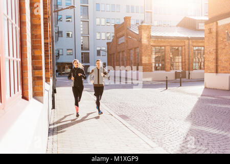 Man and woman running along street in Stockholm, Sweden - Stock Photo