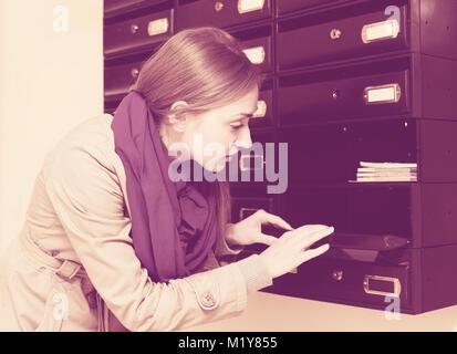 Sad girl in coat and scarf posing near empty mailbox - Stock Photo