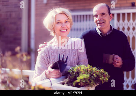 Joyful smiling elderly woman with horticultural sundry and aged man drinking tea in patio - Stock Photo