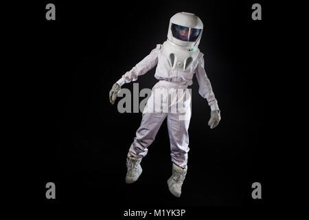 Astronaut in space, in zero gravity on black background. - Stock Photo