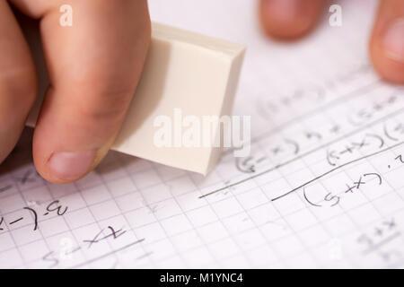 Hand with White Ruber Eraser on White Paper. Mistake Erase Concept. - Stock Photo