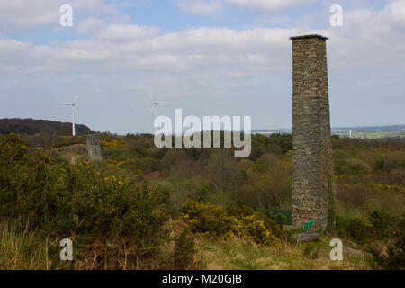 An old industrial chimney stack with modern wind turbines in the background at the old lead mines site at Whitespots - Stock Photo